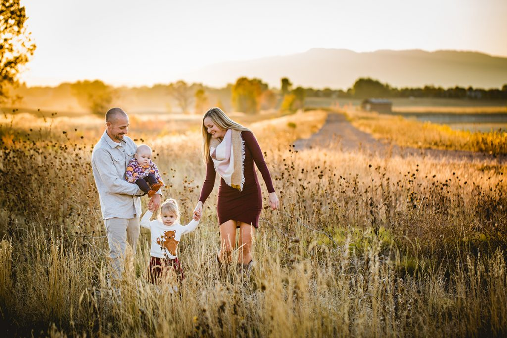 A family of four walks together in a field in Fort Collins as a part of their photography session