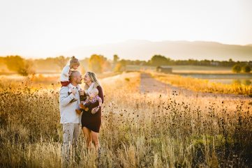 A family stands in a field together in east Fort Collins as the sun sets over the Colorado foothills
