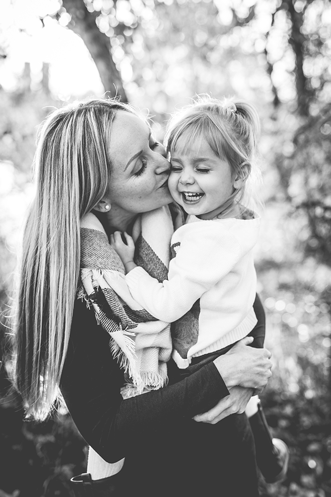 Black and white portrait of a mom kissing her little girl during their family photo session in Fort Collins