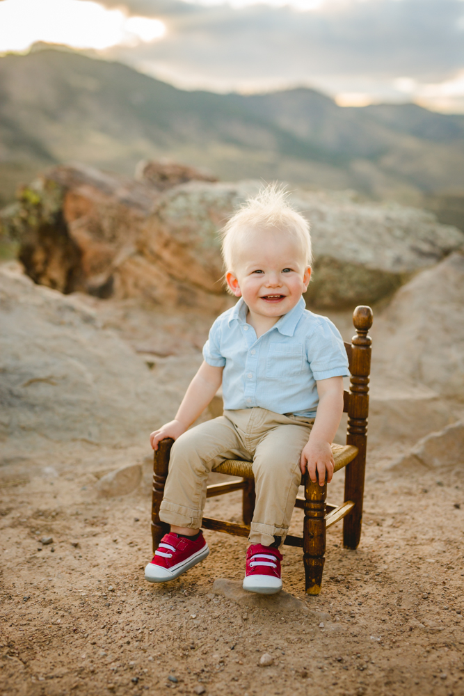 A little boy sits on a chair in the mountains as he poses for his photoraphy session in Colorado