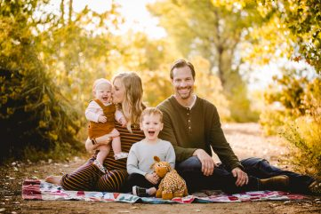 A family of four sits on a blanket in the golden fall leaves during their Fort Collins family photo session