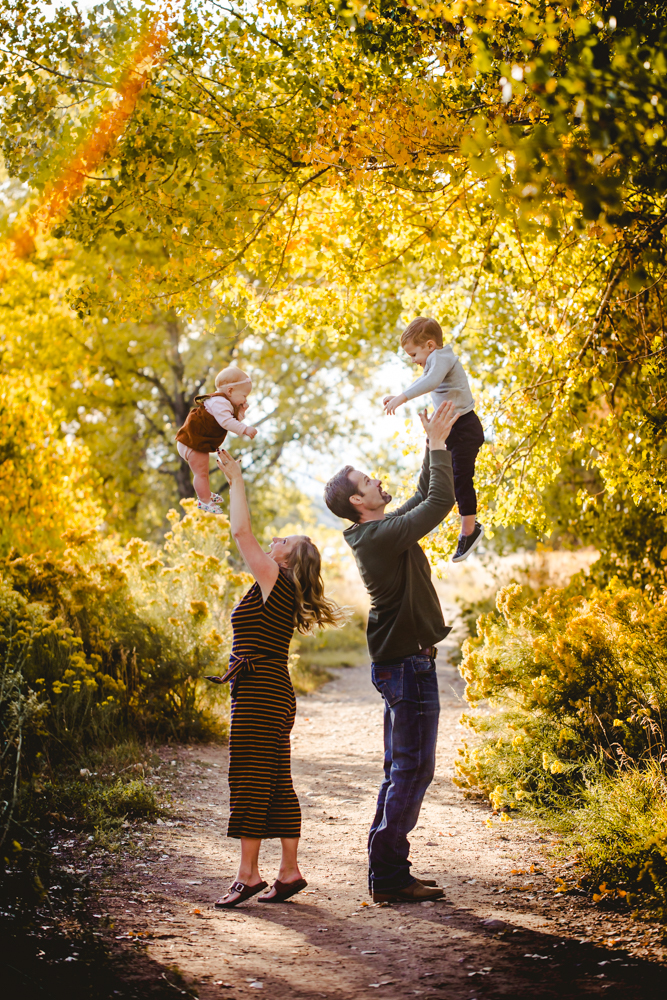 A mom and dad throw their kids in the air in a fall photo taken by Becky Michaud, photographer in Fort Collins, Colorado