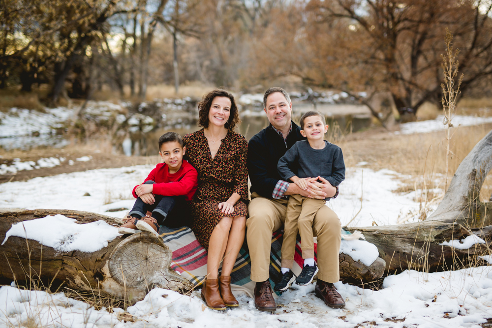 A family of four sits on a long in the snow at Lee Martinez Park in Fort Collins for their family photography session