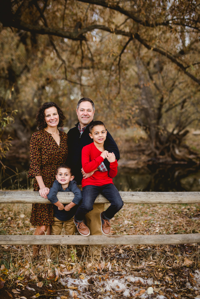 Family photo of parents and two boys on a fence in Fort Collins