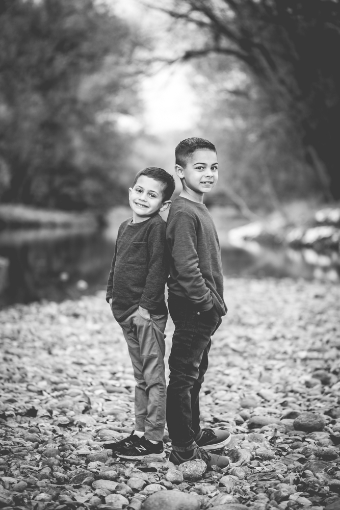Black and white photo of two brothers standing by the Poudre River in a portrait taken in Fort Collins, Colorado in the winter