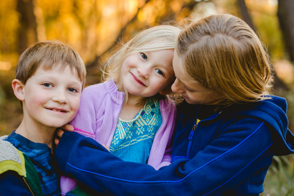 Three siblings play together during their family photography session in the fall in Fort Collins