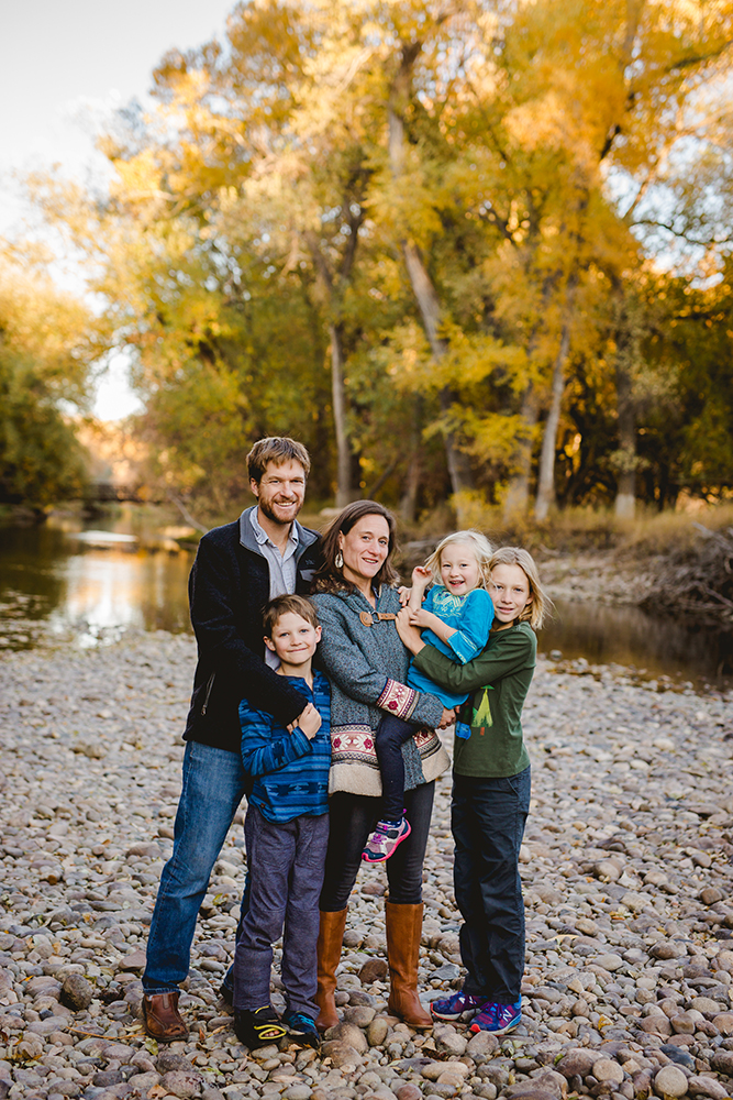 Photo of a family of five taken by the Poudre River in the fall