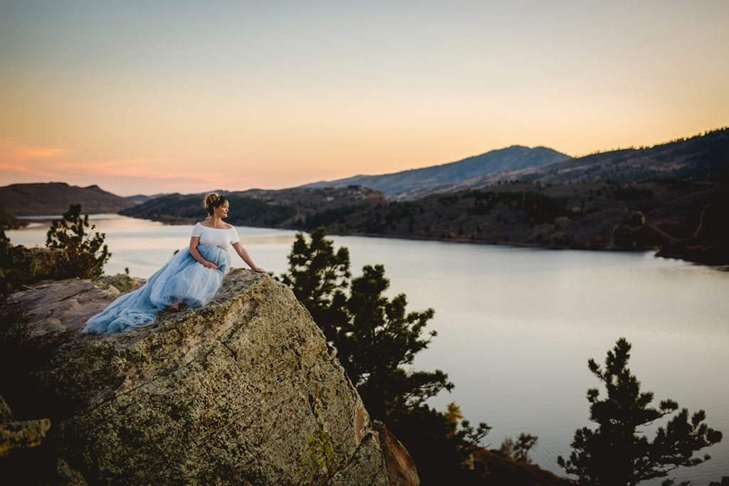 A mom looks out over Horsetooth Reservoir during her maternity photo session