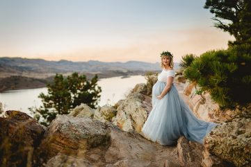 An expectant mother stands above Horsetooth Reservoir as she poses for her maternity photography session