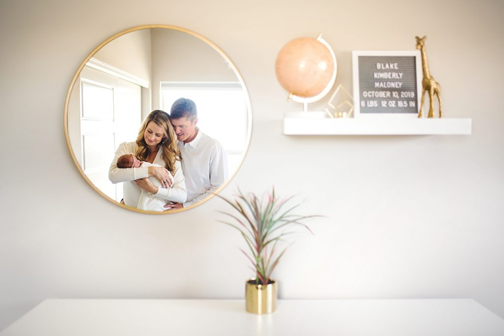 a new family of three is reflected in a mirror in the baby's Loveland, Colorado nursery