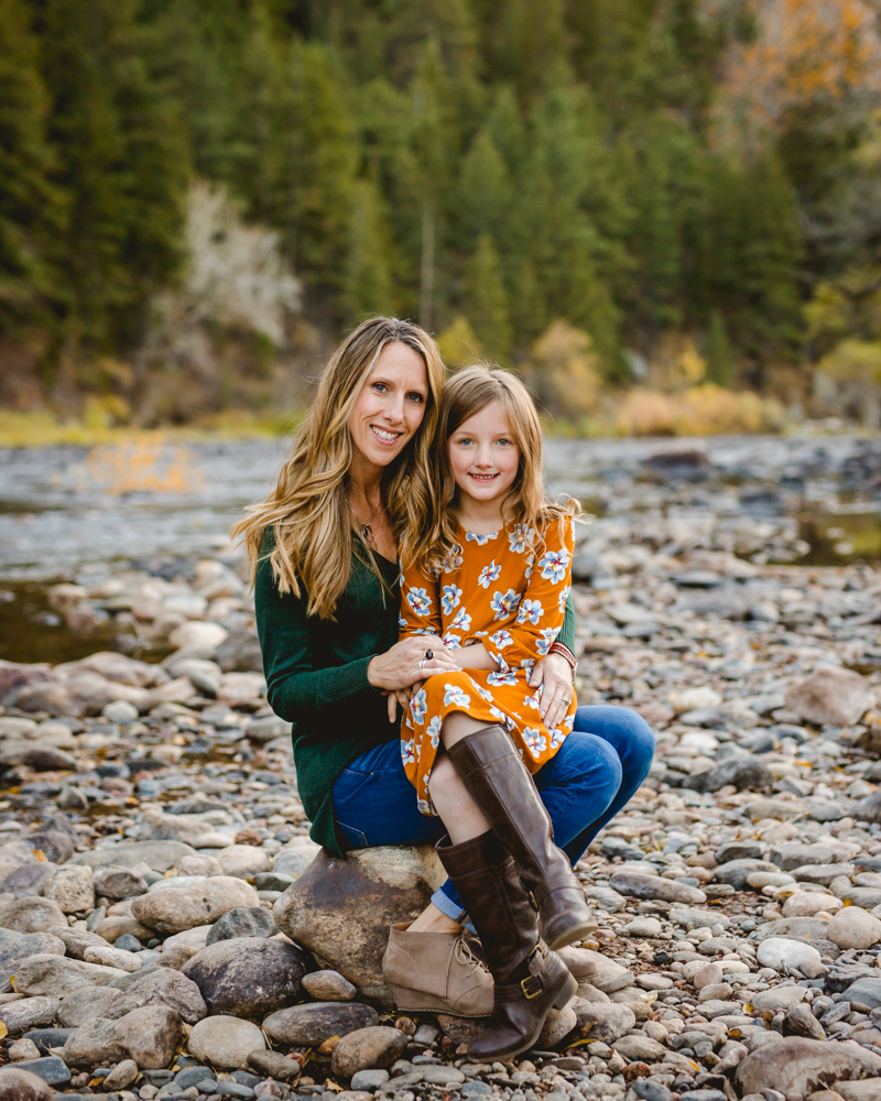 A mother and daughter sit on a rock together at Picnic Rock in the Poudre Canyon during their family photography session