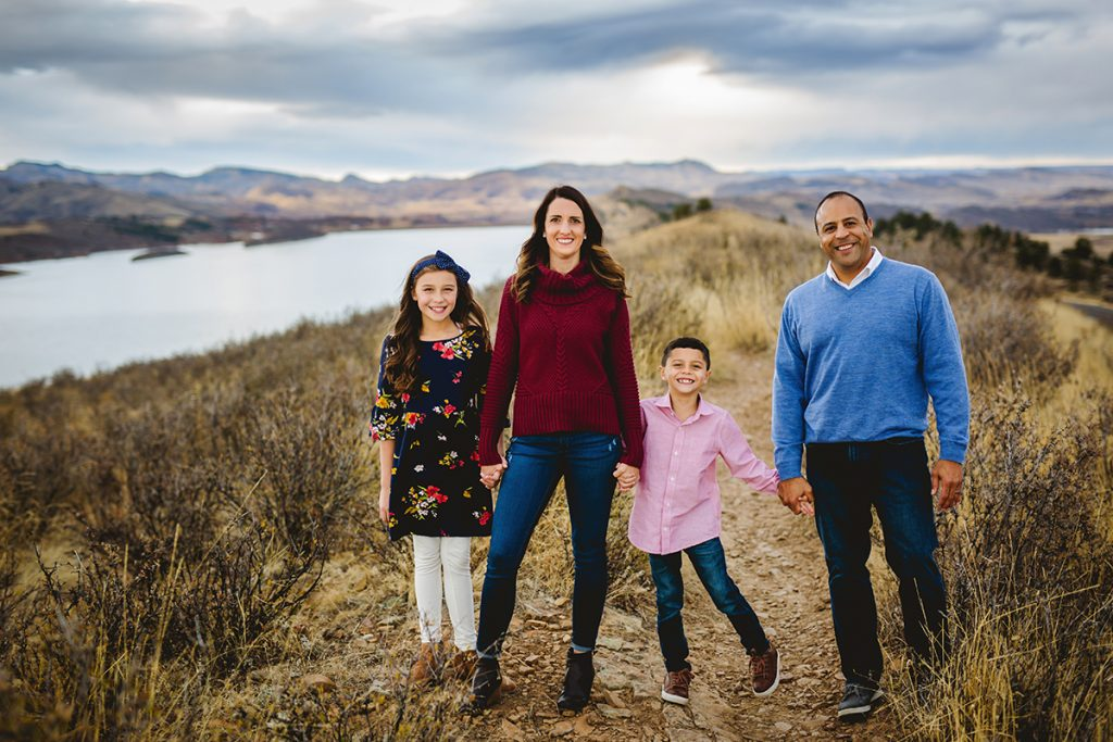 A family of four stands on a ridge at Horsetooth Reservoir during their photography session