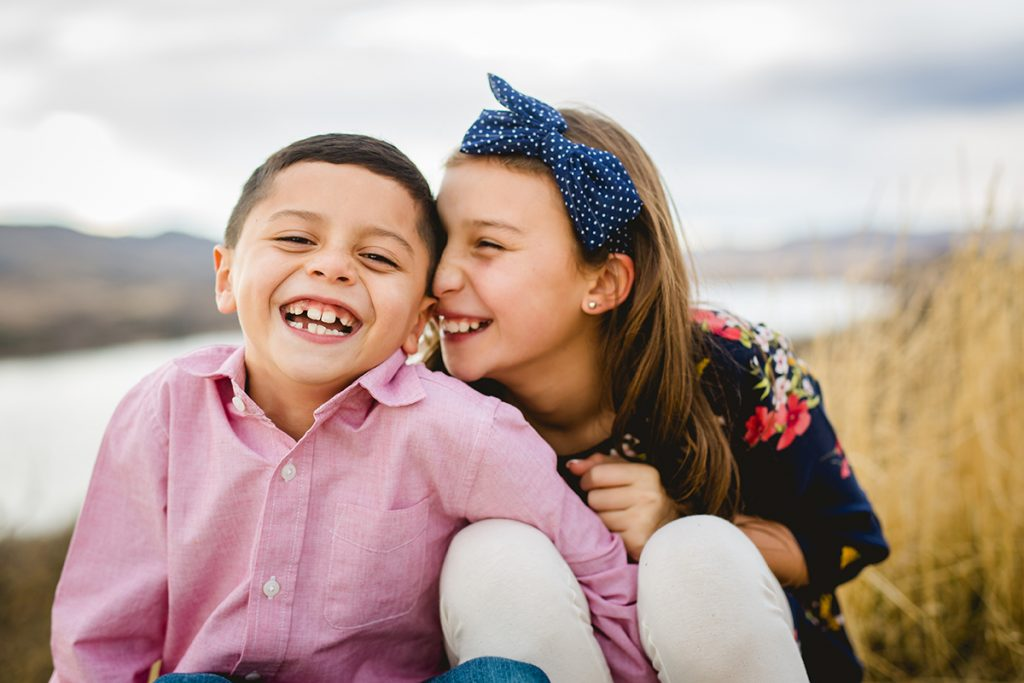 A brother and sister laugh together during their family portrait session