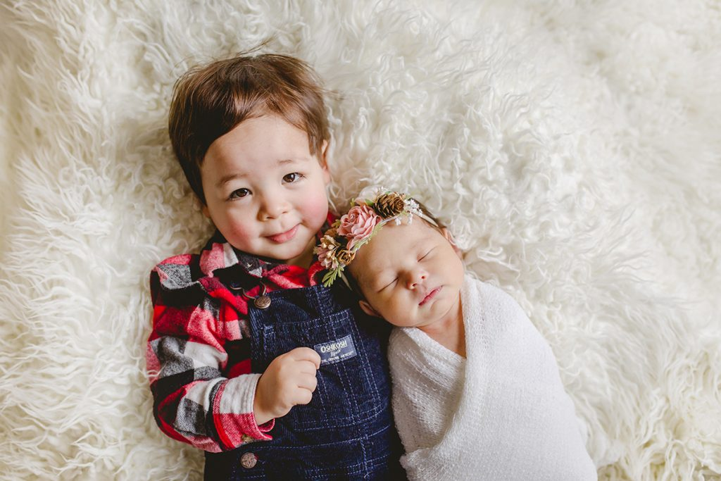 A little boy smiles as he holds his new baby sister during her Fort Collins newborn photography session