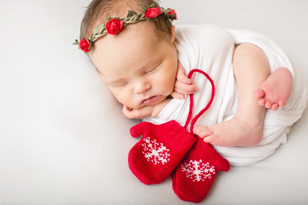 Newborn photo of a baby with red mittens and a red flower crown taken by Becky Michaud, Fort Collins photographer