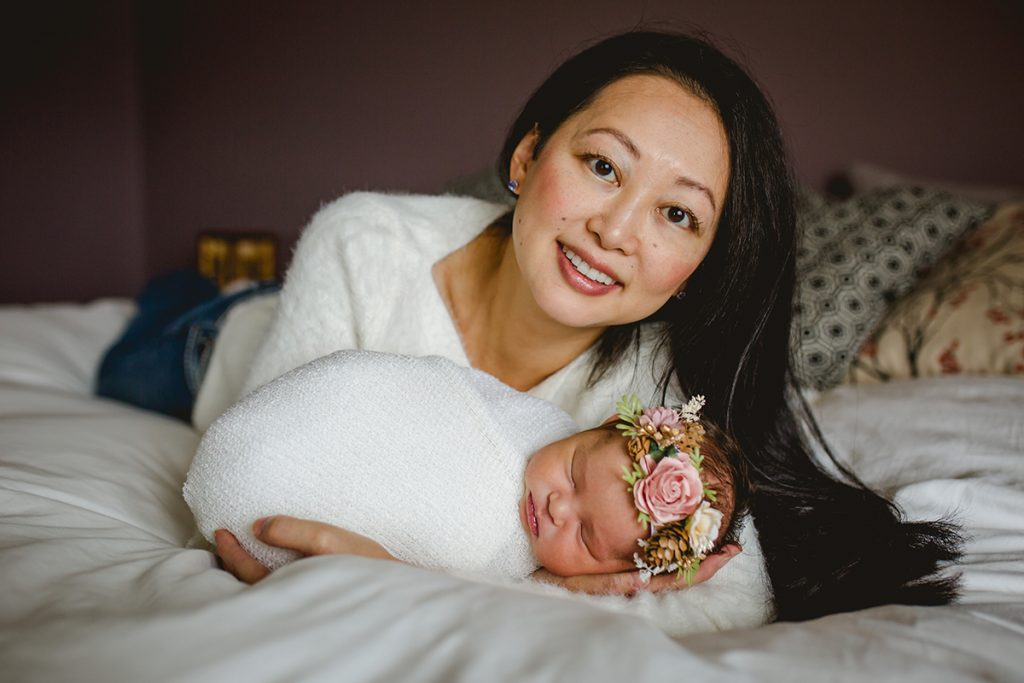 A mom poses with her baby girl on their bed in her Fort Collins, Colorado in home newborn photography session