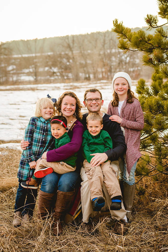 A family of six sits in a snowy field in Fort Collins for their family photo session
