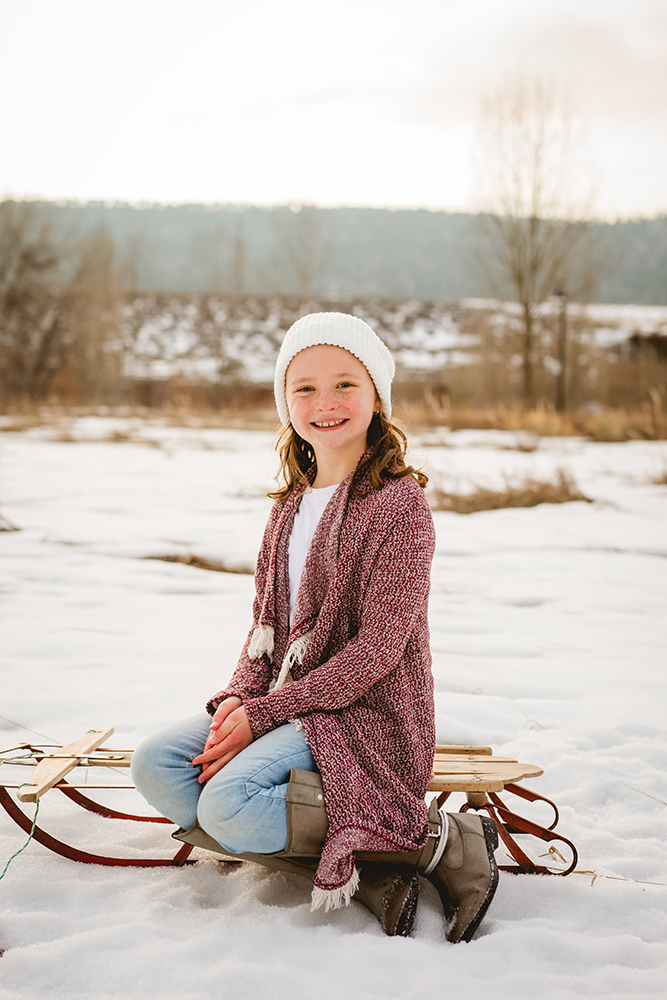 A girl sits on an antique sled as she poses for a portrait in Fort Collins, Colorado