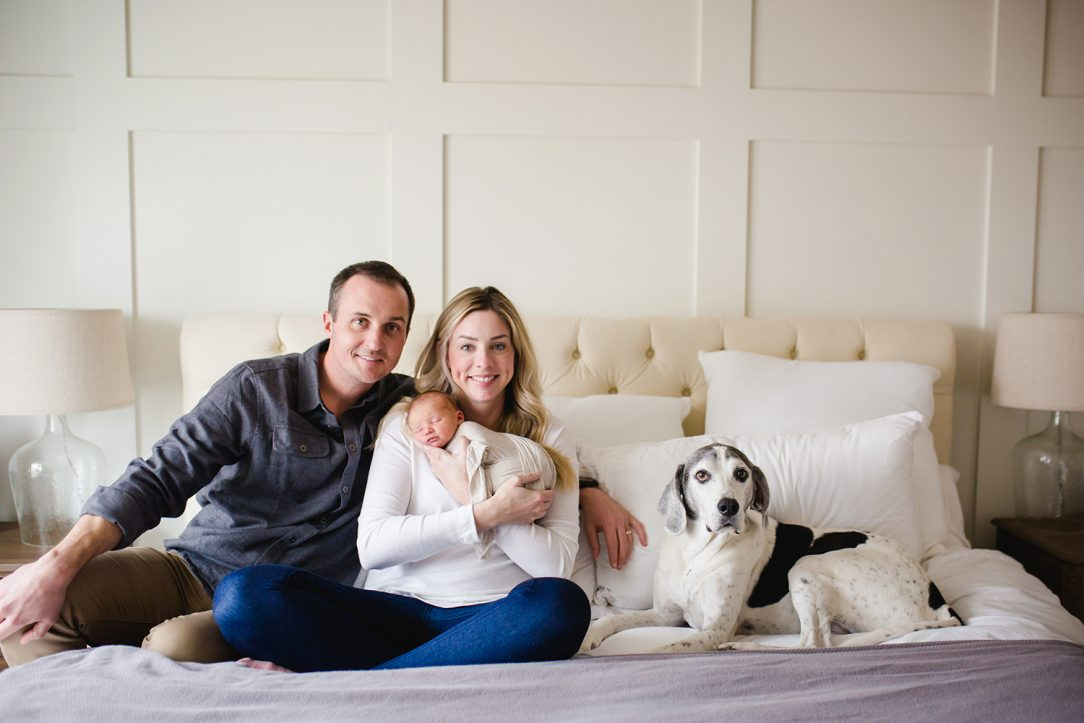 New parents pose with their newborn and their dog on their bed during their newborn photo session in their Colorado home