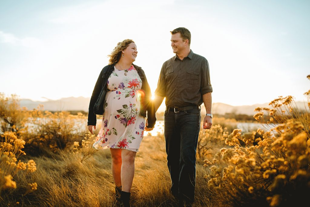 Maternity photo of a couple walking in a field together in Loveland Colorado
