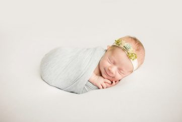 Smiling newborn lying on a white blanket wearing a succulent headband