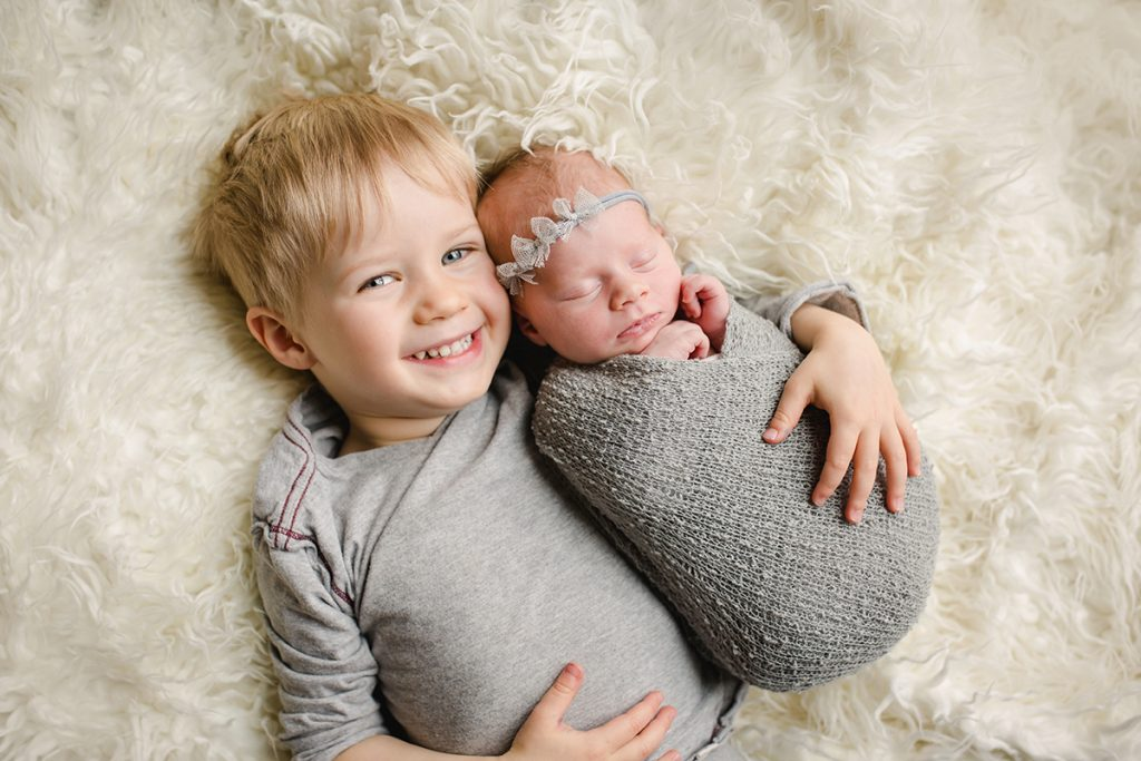 A big brother snuggles with his newborn sister during her photography session in their Fort Collins home