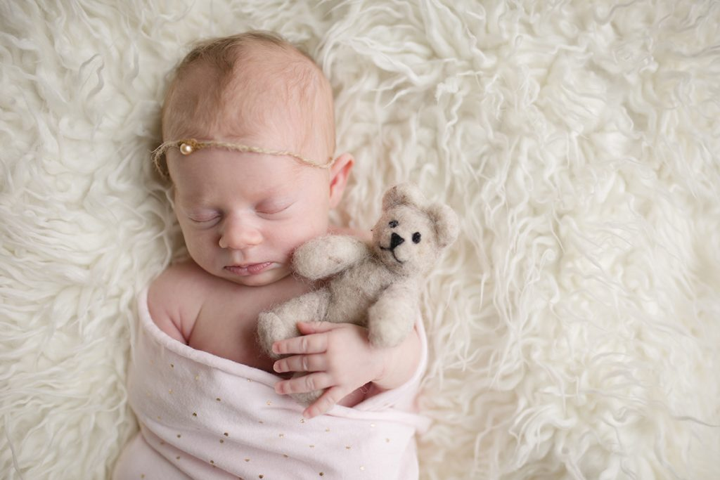 A newborn baby girl holds a teddy bear during her newborn photo session in her home in Fort Collins, CO