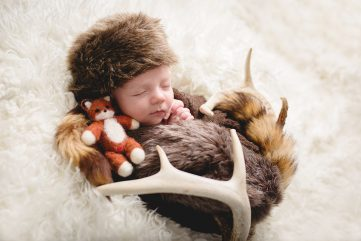 Newborn baby boy wearing a coonskin cap with a stuffed fox and elk antlers
