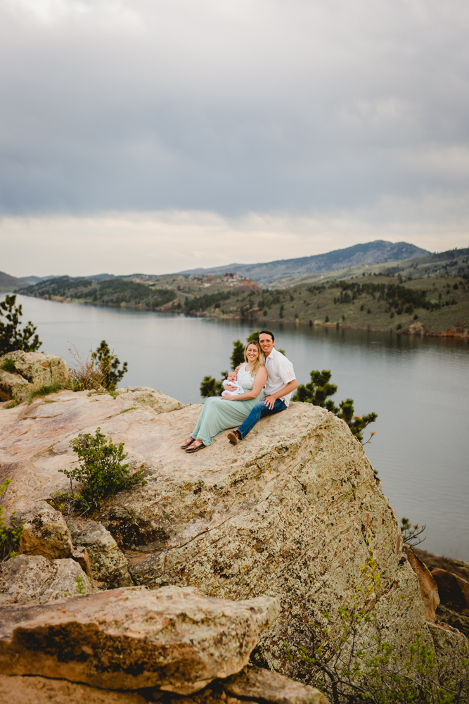 A family of three poses for their photo shoot at beautiful Horsetooth Reservoir
