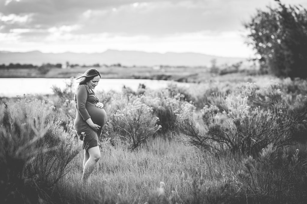 Black and white maternity photo of a woman standing in a field in Loveland, Colorado