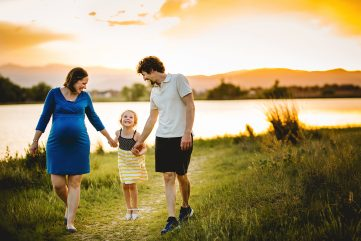 A family of three walks together by the lake during their maternity photo session in Loveland Colorado