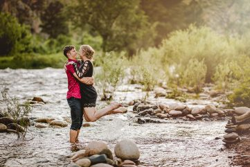 A couple plays in the Poudre River during their engagement photo shoot at Picnic Rock in Northern Colorado