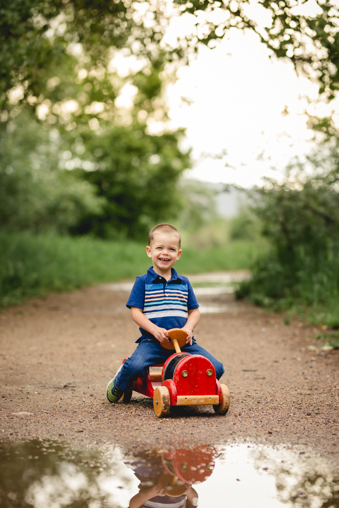 A boy rides a vintage fire truck toy in a photo taken by Becky Michaud, Fort Collins photographer