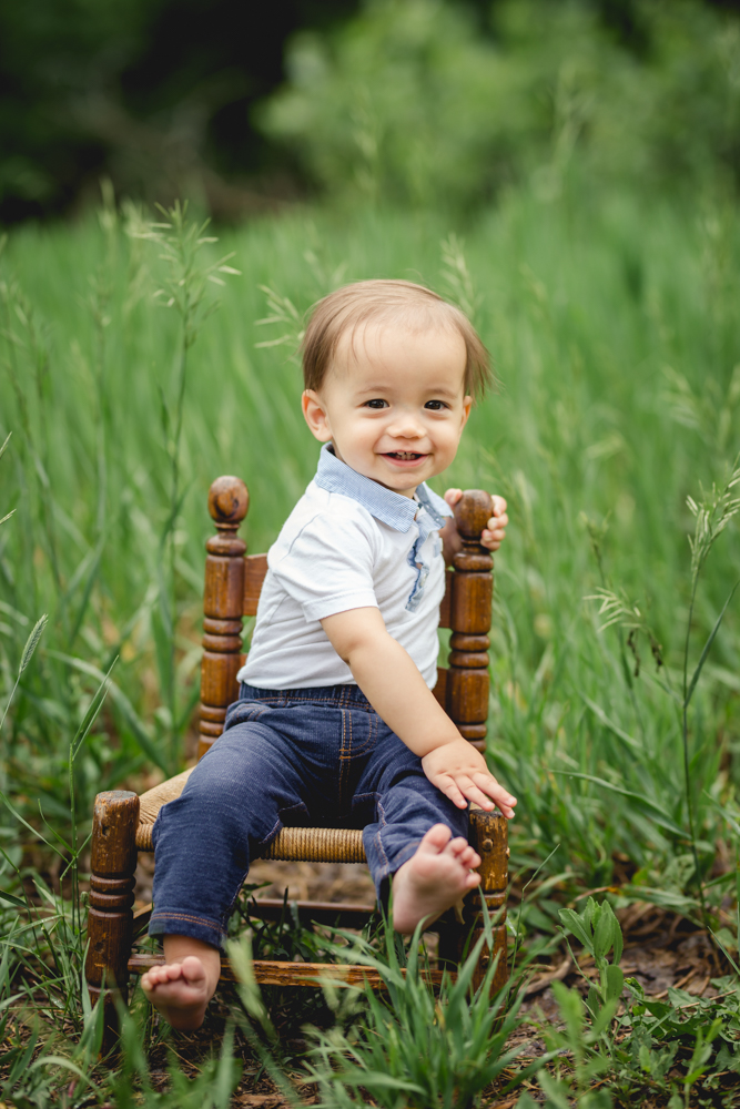 A baby smiles as he sits on a wooden chair in his outdoor photography shoot in Fort Collins, Colorado