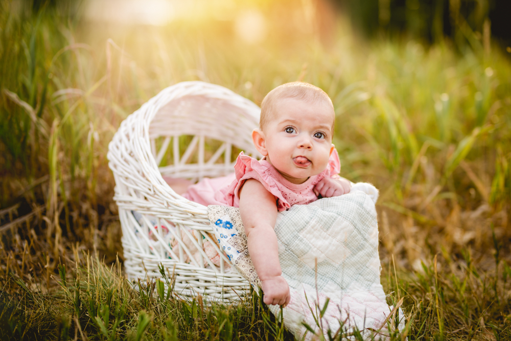 Baby girl plays with her tongue as she sits in a white wicker basket in a photo taken by Becky Michaud, Colorado baby photographer