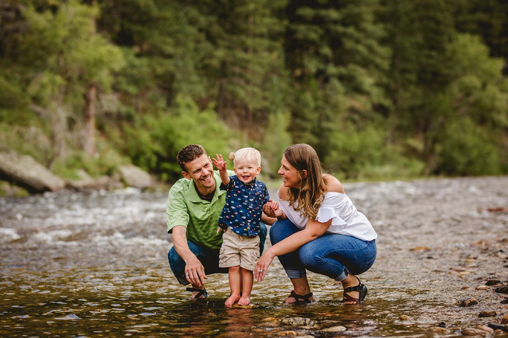 A little boy plays in the river with his parents during their photography session on the poudre river