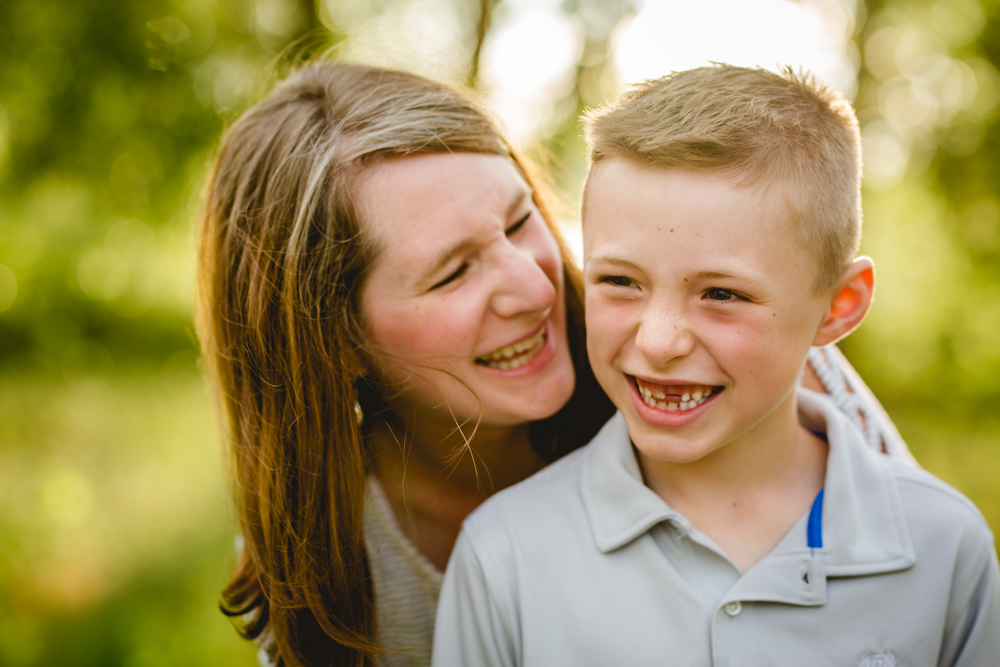 A mom and son laugh together during their family photo session in Northern Colorado