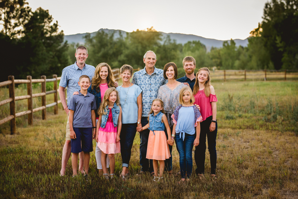 Photo of an extended family posing by a fence in front of the foothills of northern Colorado