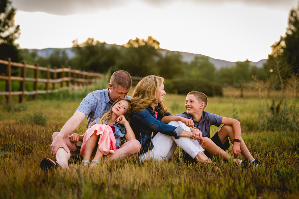 unposed photo of a family of four in a field with the foothills of Fort Collins behind them