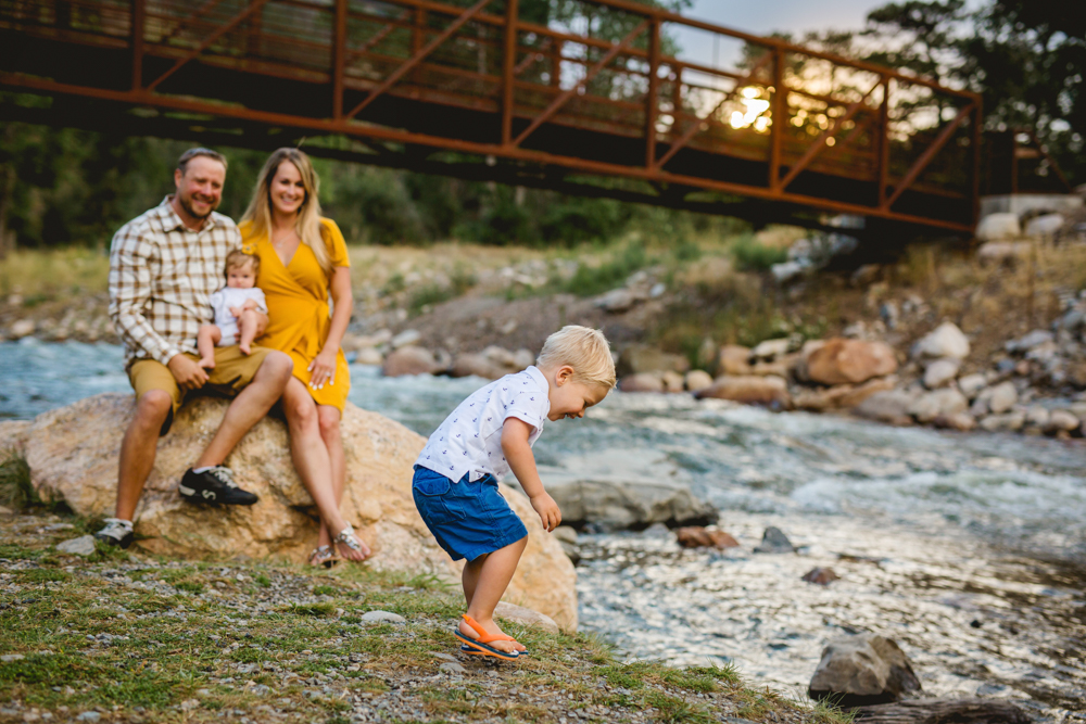 Parents watch their little boy throw rocks in the river in a photo taken by Becky Michaud, Fort Collins photographer