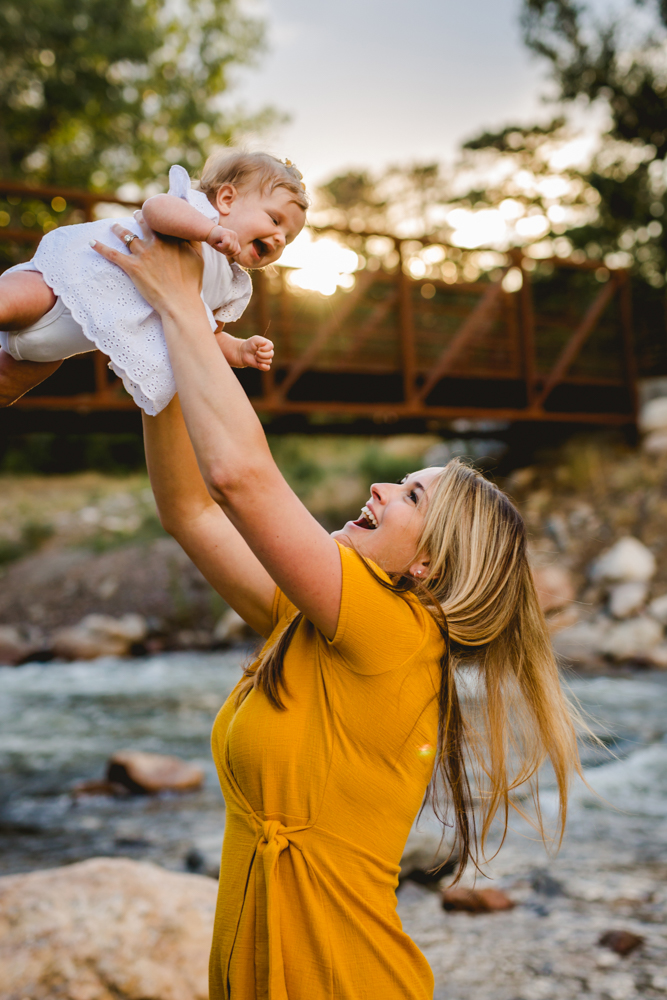 mom and baby girl play together during their family photo session by a river in the mountains