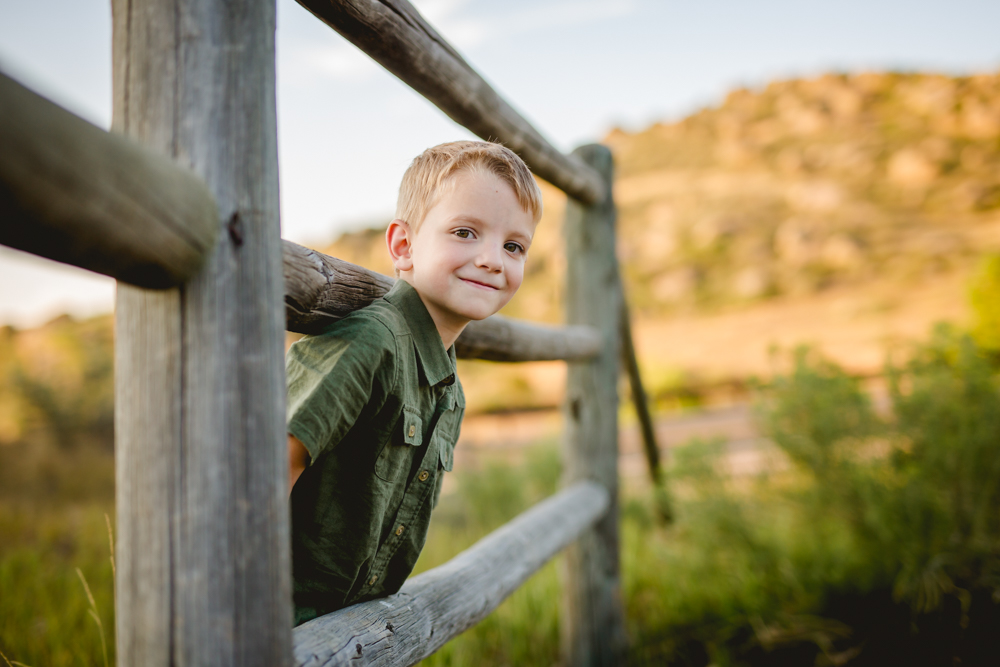 A little boy peeks through a fence as he poses for his portraits in Bellvue, Colorado