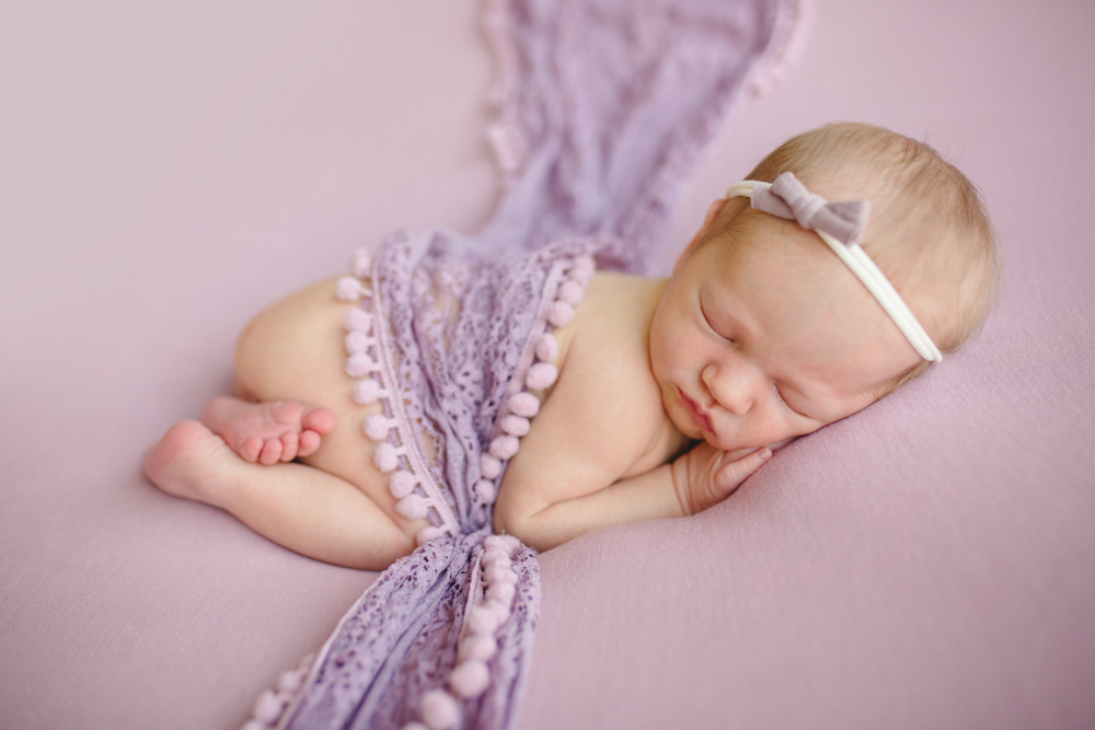 Newborn baby with a purple lace wrap in a photo taken in her home in northern Colorado