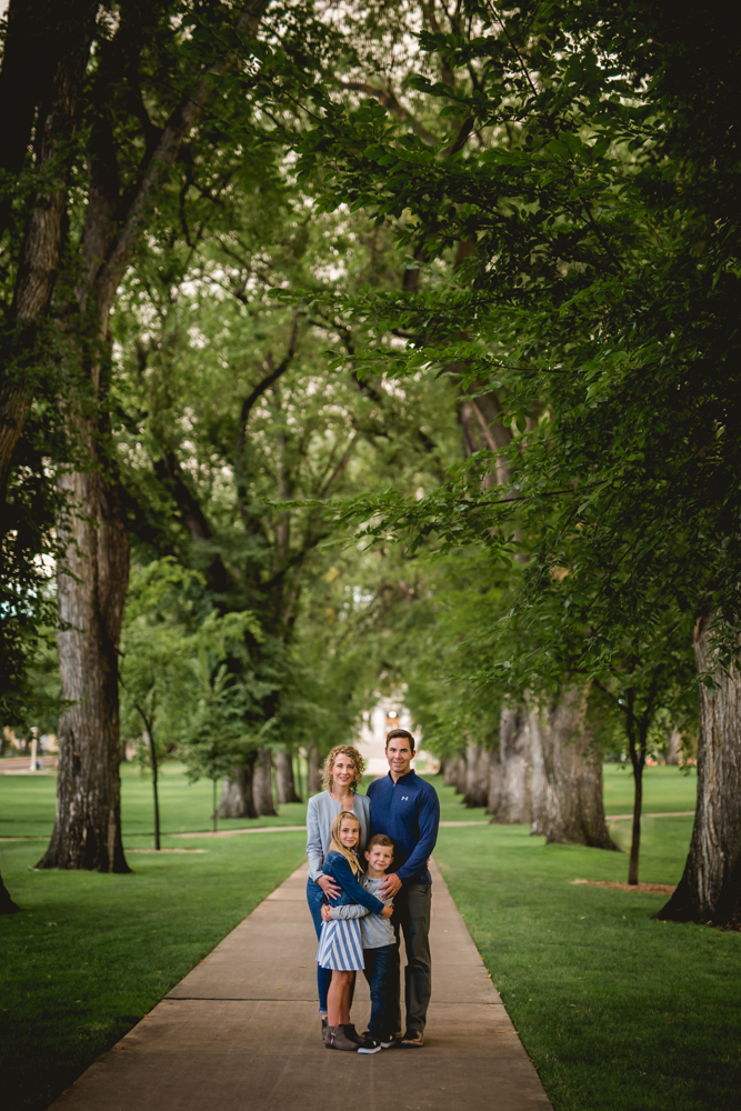 a family poses for their photos on a path lined with large trees at the Oval at CSU