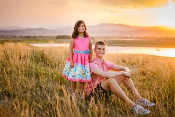 A brother and sister sit in the grass together as the sun sets over the mountains at TPC Colorado Course