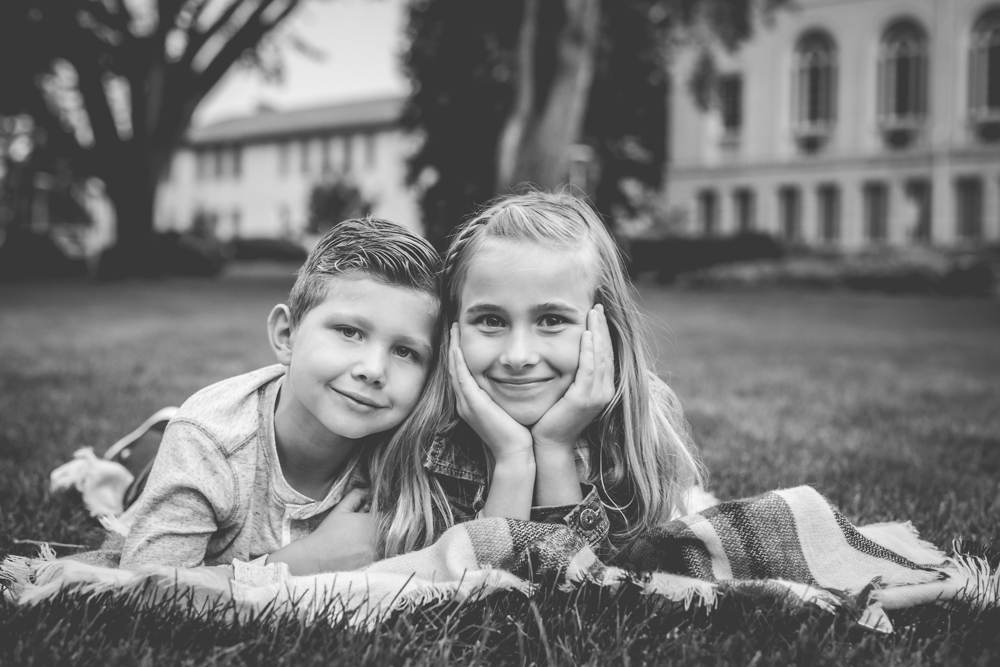 black and white photo of a brother and sister laying on a blanket during their Fort Collins family photo session