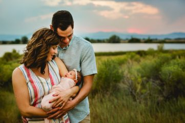New parents admire their newborn baby girl during their family photo session