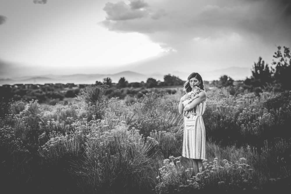 Monochromatic photo of a mother holding her newborn baby in a field in Loveland, Colorado