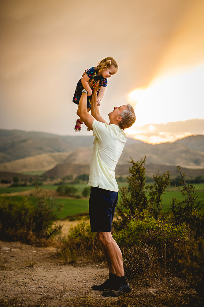 A dad lifts his little girl into the air against the backdrop of the foothills of Bellvue, Colorado