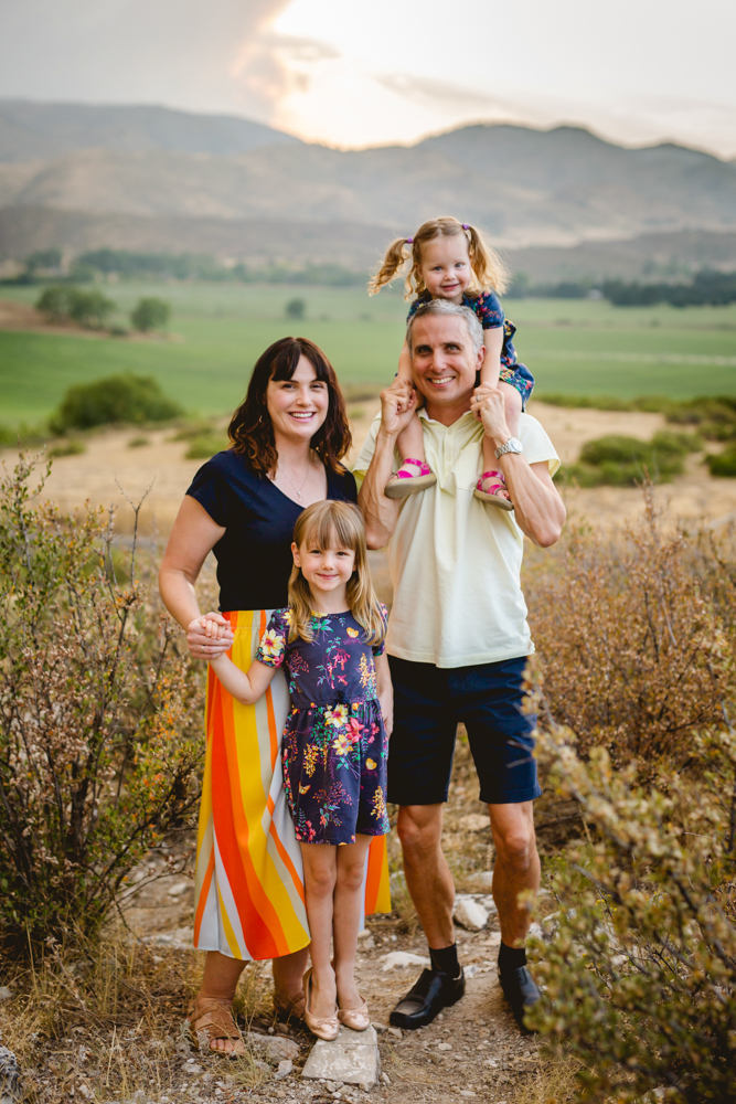 A family of four poses for their family photo in the foothills of Fort Collins